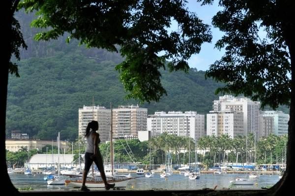 Mulher caminhando na orla da praia do Rio de Janeiro.