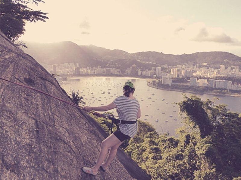 Mulher fazendo rapel no morro da Urca no Rio de Janeiro