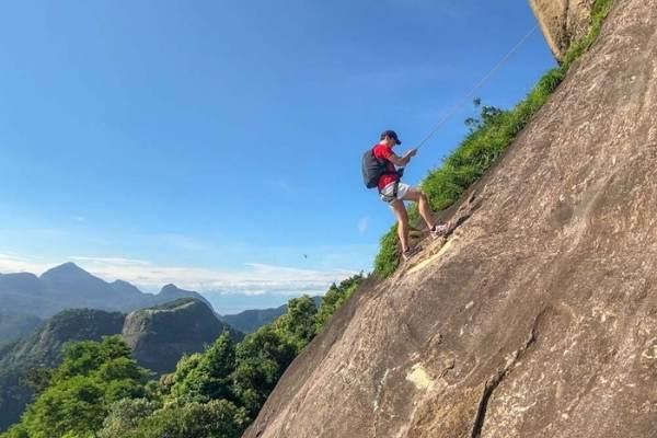 Homem fazendo rapel na pedra da Gávea.