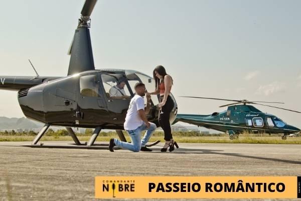Casal na frente do helicóptero.