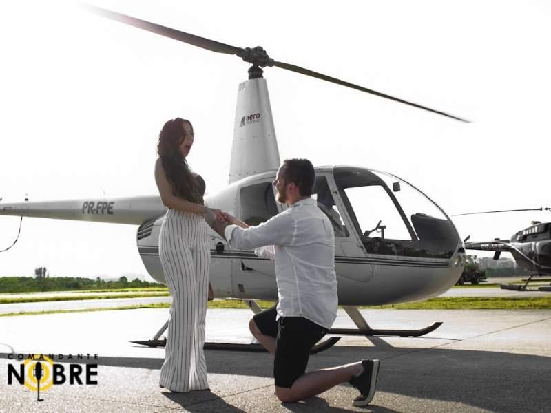 Homem ajoelhado pedindo mulher em casamento ao lado do helicóptero.